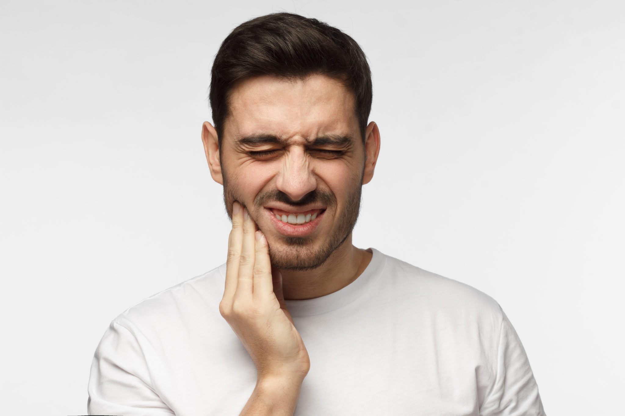 A man suffering from TMJ jaw pain.
