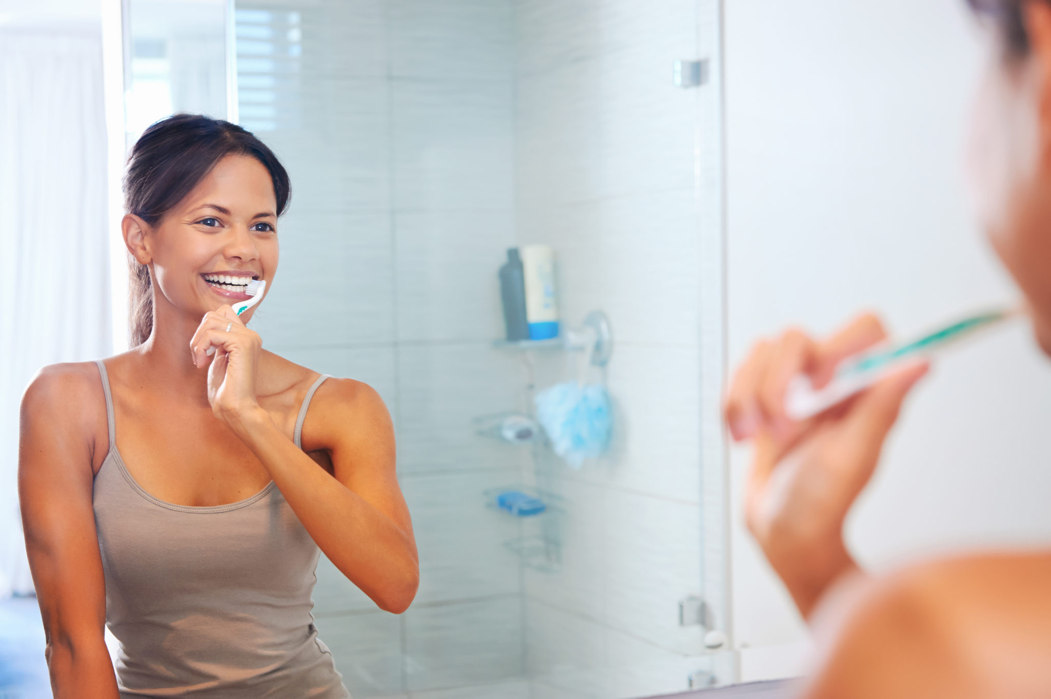 Image of a woman brushing her teeth.